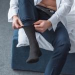 Mann mit offenen Hemd zieht sich Socken an.