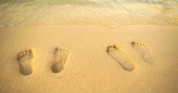 Zwei paar Fußabdrücke im Sand nebeneinander am Meerwasser